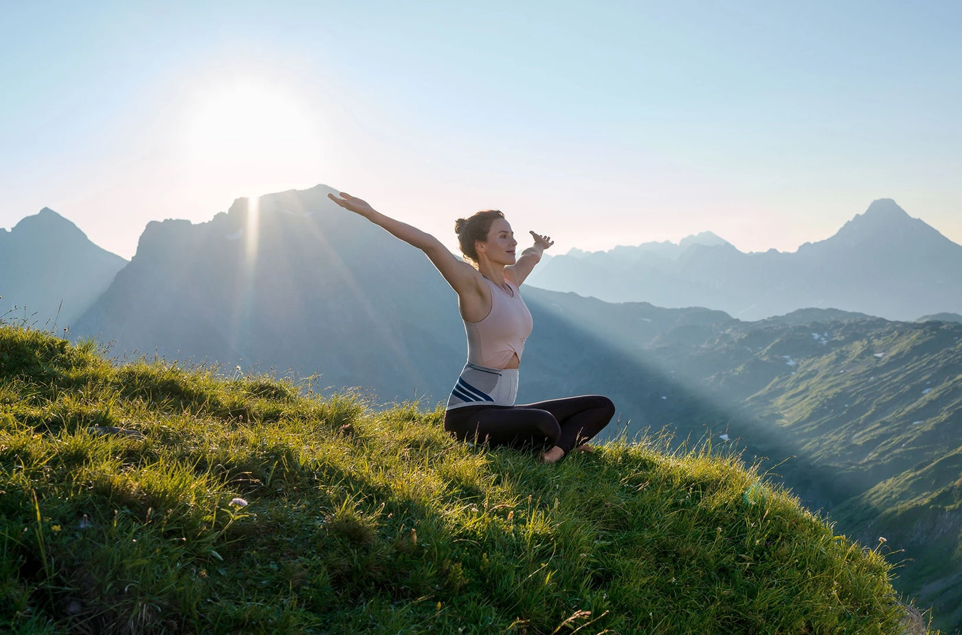 Woman sitting on grass on top of a mountain, spreading her hands out, and wearing a back brace made by Bauerfeind.