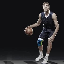 Man bending and playing basketball wearing all black dri-fit jerseys, and basketball knee support by Baurfeind Australia.