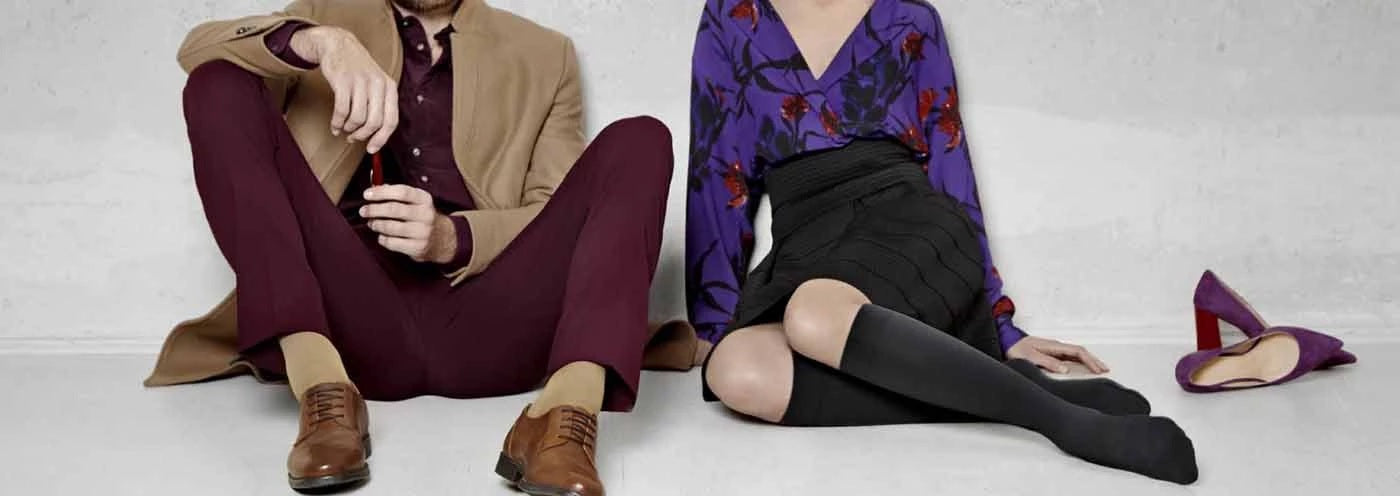 Close-up of a woman and man sitting on the floor wearing a caramel and black coloured socks. It is one of Bauerfeind Australia's best compression socks.