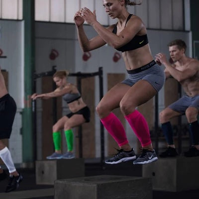 Group of people participating crossfit wearing red, green, black and white crossfit compression sleeves by Baurfeind Australia.