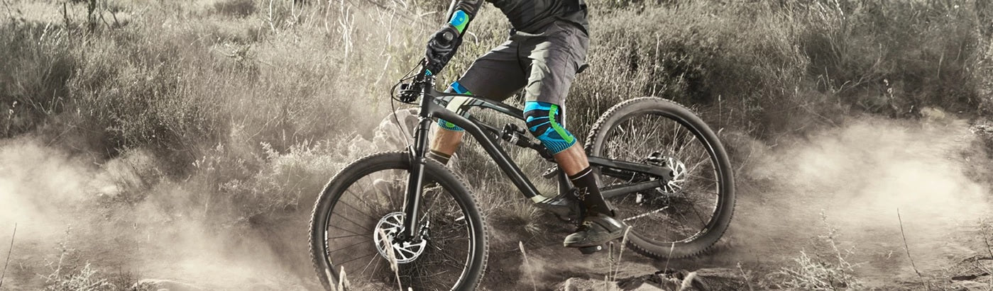 A person riding a bicycle wearing black and grey cycling gears, and cycling supports and straps. It is one of the best biking supports and braces of Bauerfeind Australia.