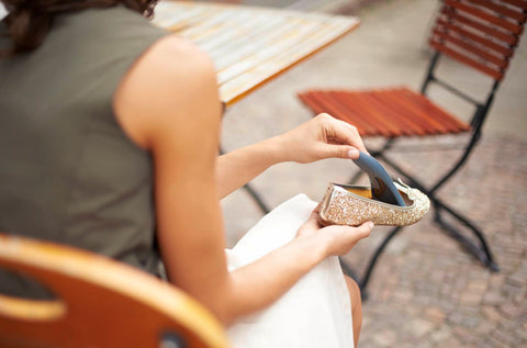Woman putting an bauerfeind insole into her shoe to help reduce the pain associated with Plantar Fasciitis