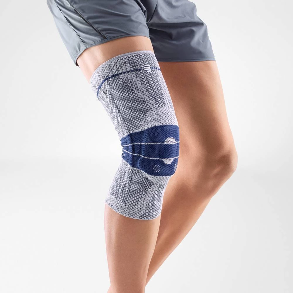 Knee brace having a colour combination of blue and grey, is wore on a right knee. With the logo of Bauerfeind that is consider as one of their best recovery knee brace which is named as GenuTrain Knee Brace.
