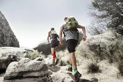 Man and woman trekking wearing grey and black dri-fit gears, and hiking ankle support by Baurfeind Australia