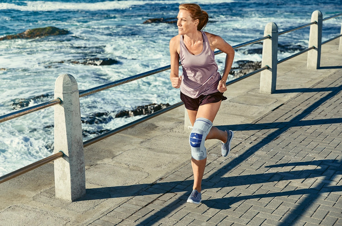 Woman running/jogging on seashore track, and wearing a knee brace made by Bauerfeind.