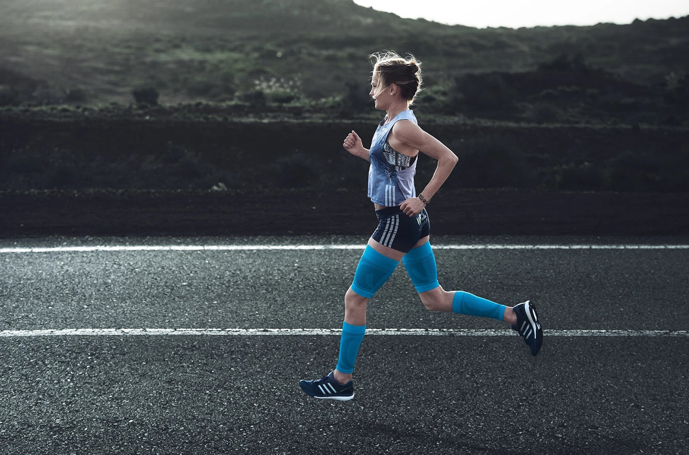 Woman running/jogging on an asphalt road, and wearing blue leg supports made by Bauerfeind.