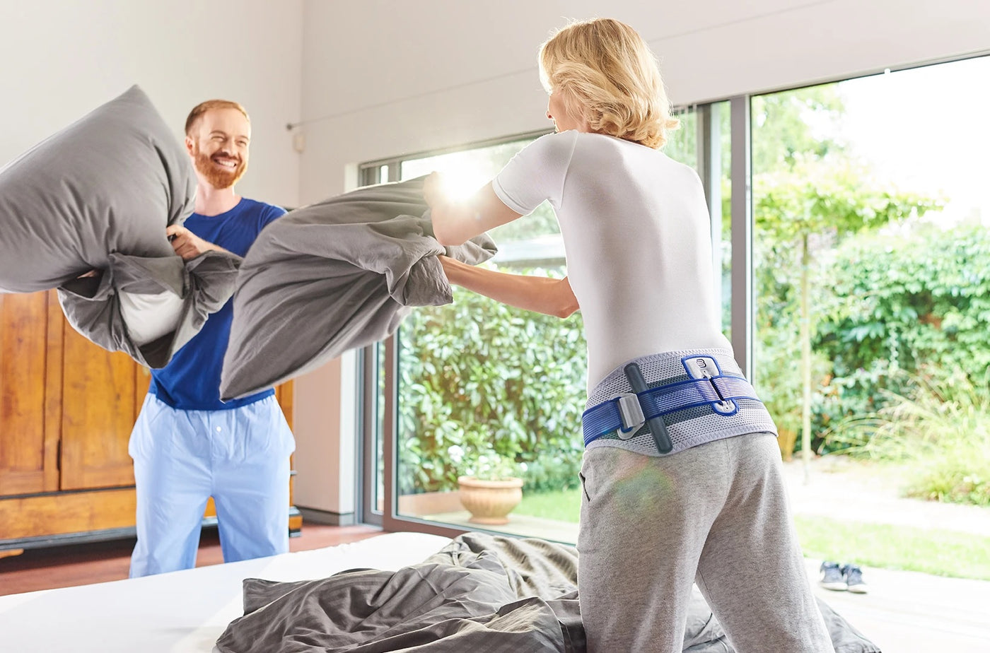 Man and woman having a pillow fight, wearing shirts and pajamas and with a medical brace and support made by Bauerfeind.