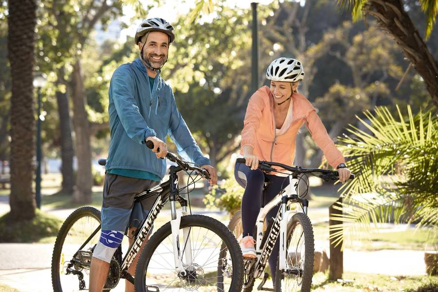 Man wearing knee support which is one of Bauerfeind Australia product and a full cycling gear along with a woman also riding on a bicycle.