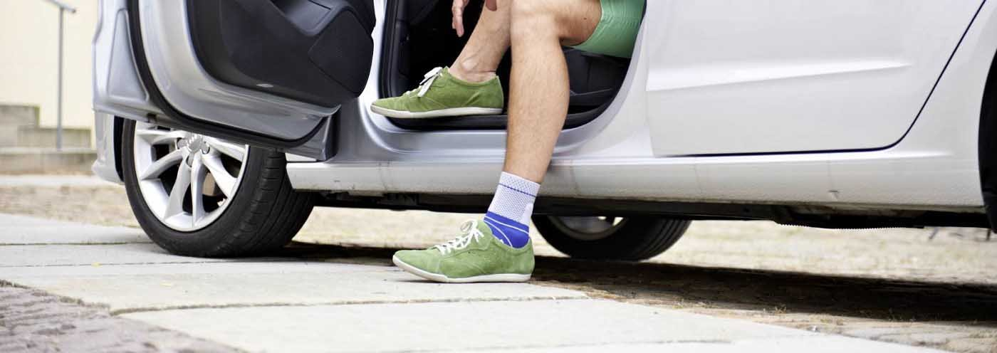 A person sitting in a car wearing a blue and grey ankle brace. It is considered one of Bauerfeind Australia's best recovery ankle brace.
