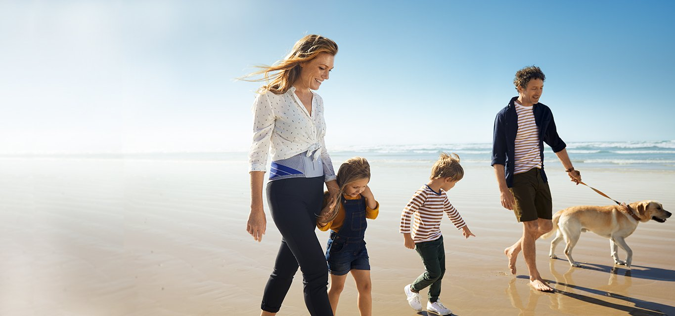 Woman wearing a back brace which is one of the recovery supports and braces of Baurfeind, and is walking on a sea shore along with her family and their dog.