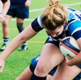 Woman tackling and playing rugby wearing a blue and white color combination dri-fit jersey and shorts, and black sports rugby knee braces by Baurfeind Australia.