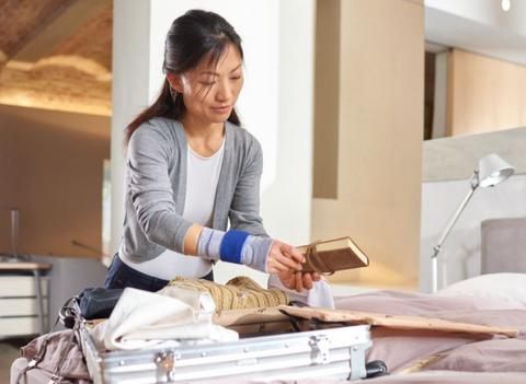 Woman wearing a Bauerfeind wrist support while packing a suitcase