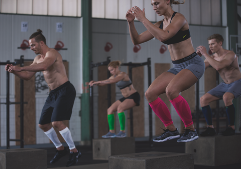 group of people doing jump squats in the gym while wearing Bauerfeind lower leg calf compression sleeves
