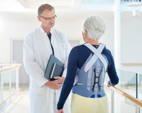 Patient wearing Bauerfeind back brace talking to a doctor