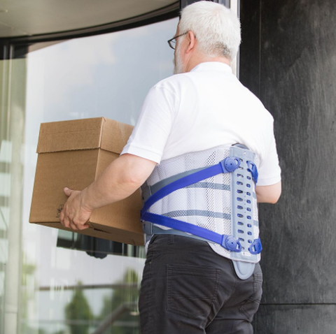 Man carrying box wearing a Bauerfeind back brace