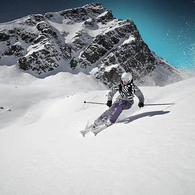 A person skiing wearing a grey, purple skiing gears, white helmet, and skiing supports and braces by Baurfeind Australia.