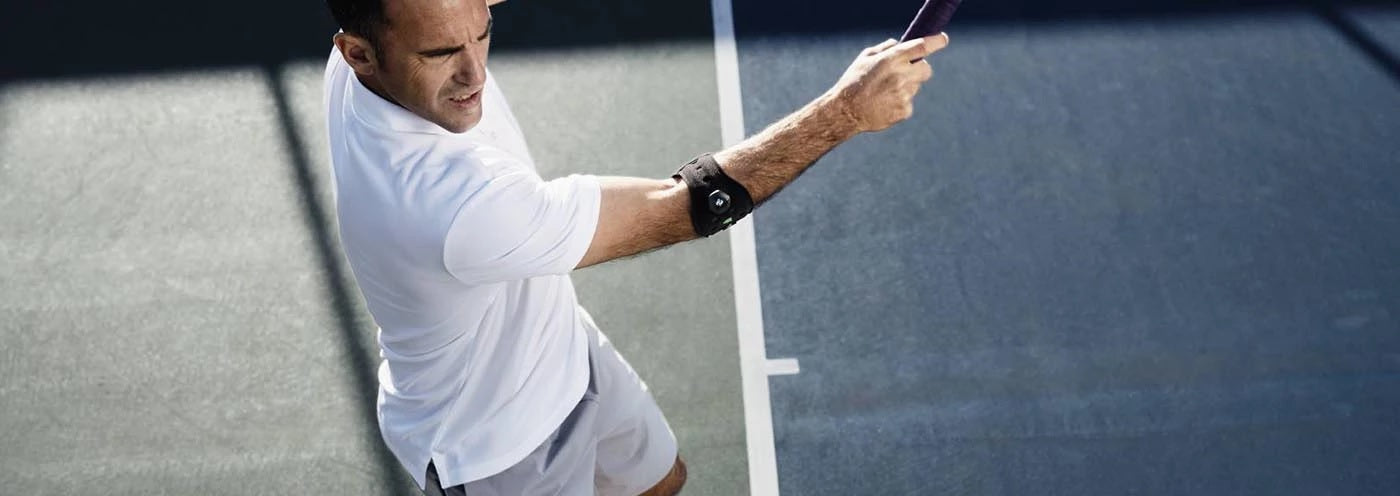 Man playing tennis wearing a white shirt, grey shorts and an elbow sports brace/support. It is one of the best sports elbow supports of Baurfeind Australia.