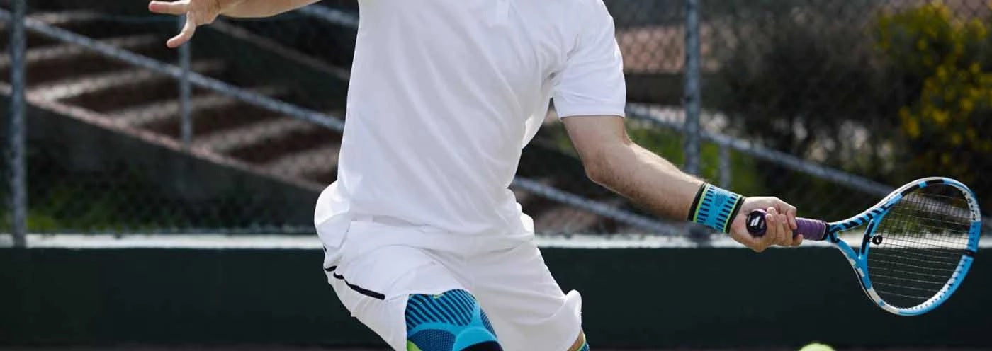 A man in an all-white jerseys playing tennis is wearing Bauerfeind Australia's sports wrist supports on his left arm.