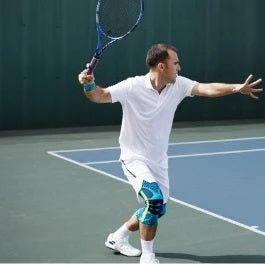 Man smashing and playing tennis wearing all white dri-fit jersey and shorts, and blue sports knee supports by Bauerfeind Australia.