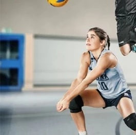 Woman bending and playing volleyball is wearing grey and black dri-fit jerseys, with volleyball knee braces by Baurfeind Australia.
