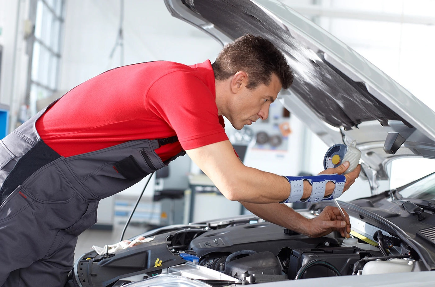 A car-mechanic wearing a red shirt and grey mechanic suit, and on his right hand is a wrist brace made by Bauerfeind.