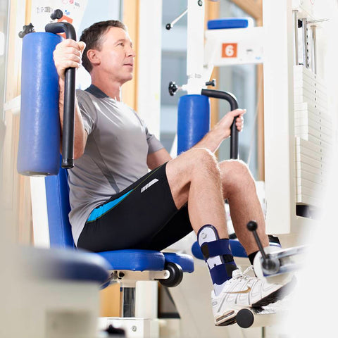 Man exercising in the gym wearing a Bauerfeind ankle brace for a sprained ankle