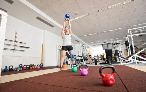 Person wearing a Bauerfeind knee brace lifting kettlebells in the gymphysiotherapy exercise