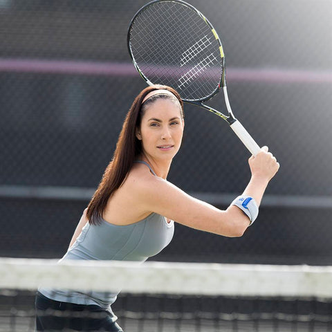 A woman wearing gray no-sleeve shirt, black shorts, white headband and is holding a tennis racket with a elbow brace having a colour combination of blue and white, is wore on right elbow. With the logo of Bauerfeind that is consider as one of their best elbow braces for Tennis.