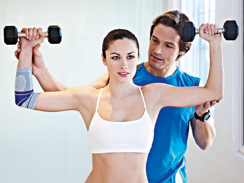 Woman exercising in the gym wearing Bauerfeind elbow support, man advising her on the exercises.