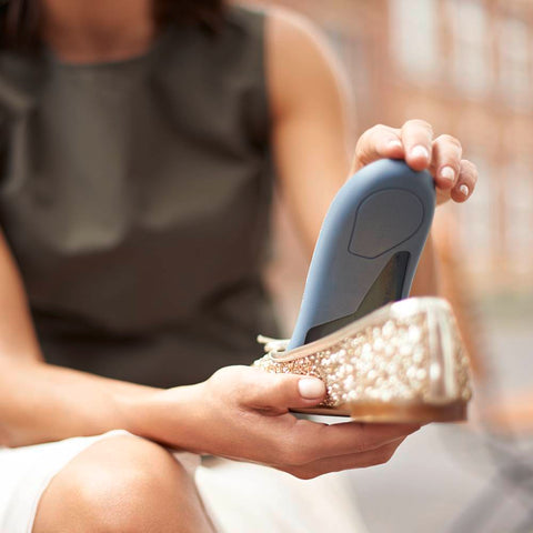 Woman putting a Bauerfeind insole into her shoe. This insole is designed to help relieve the pain associated with flat feet.