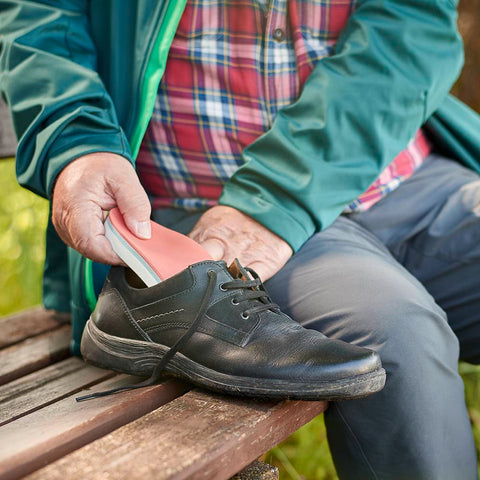 Person inserting diabetes foot orthosis pad into their shoe