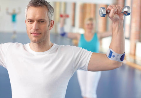 Man lifting weights in the gym wearing a Bauerfeind elbow strap to help golfers elbow