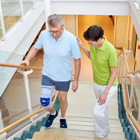 Man walking upstairs while wearing a Bauerfeind knee brace