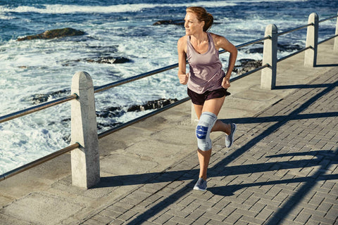 Woman running while wearing a Bauerfeind knee support for knee injury