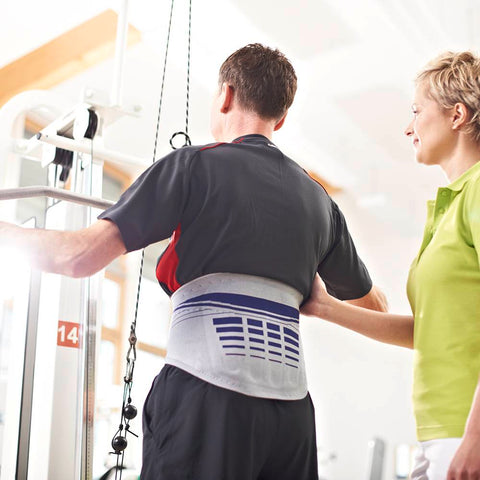 Person exercising in a gym wearing a Bauerfeind lower back brace for relieve pain