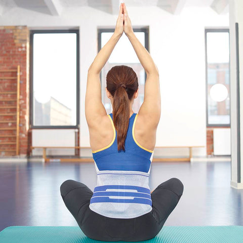 Lady sitting on yoga mat wearing a Bauerfeind back brace for back pain