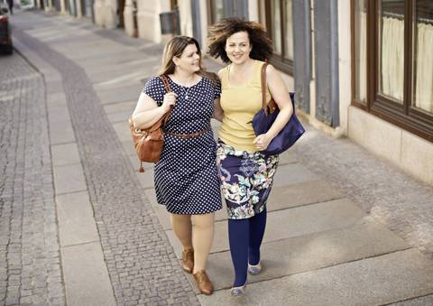 Two women wearing compression garments walking down the street