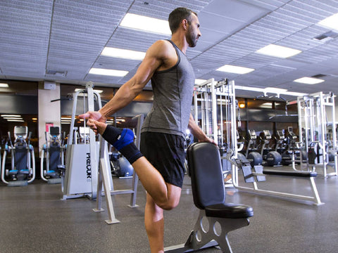 man stretching his leg in the gym while wearing an ankle brace: an injury-free return to the gym