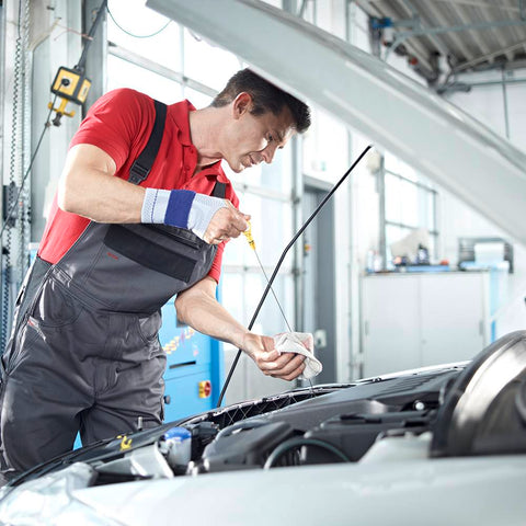 Man fixing a car while wearing a Bauerfeind wrist brace for injury prevention and management