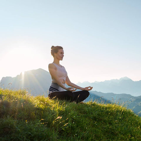 Woman sitting on a hill meditating wearing a Bauerfeind back brace.