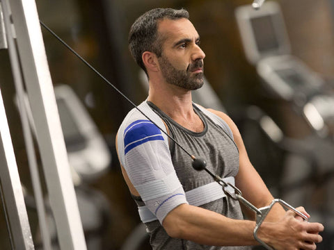 Male wearing Bauerfiends OmoTrain shoulder braces while exercising in the gym