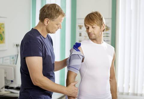 Male being fitted for the Bauerfiend OmoTrain shoulder brace by a specialist