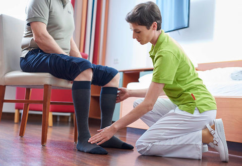 Person wearing compression stockings and specialist carrying out haglund's deformity treatment