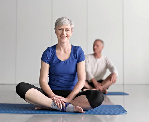 Woman wearing a Bauerfeind ankle brace while sitting on a yoga mat. with crossed legs.