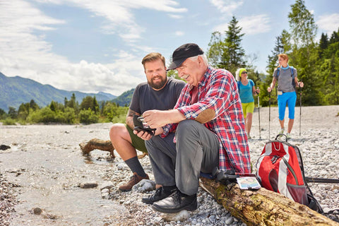 Group exercising outdoor. Man with diabetic foot taking a rest on a log.