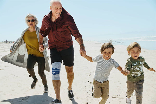 Family on beach with knee brace