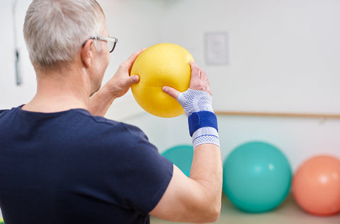 Man wearing a Bauerfeind wrist brace while doing a wrist strengthening exercise. The wrist brace helps reduce pain and manage the symptoms associated with EDS