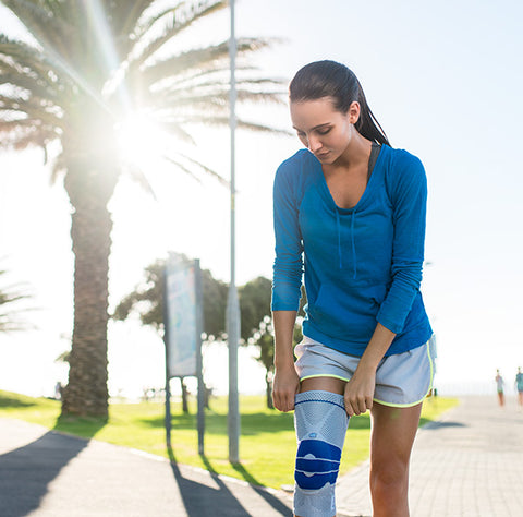 Woman pulling on a Bauerfeind knee brace to stop old knee injuries flaring up
