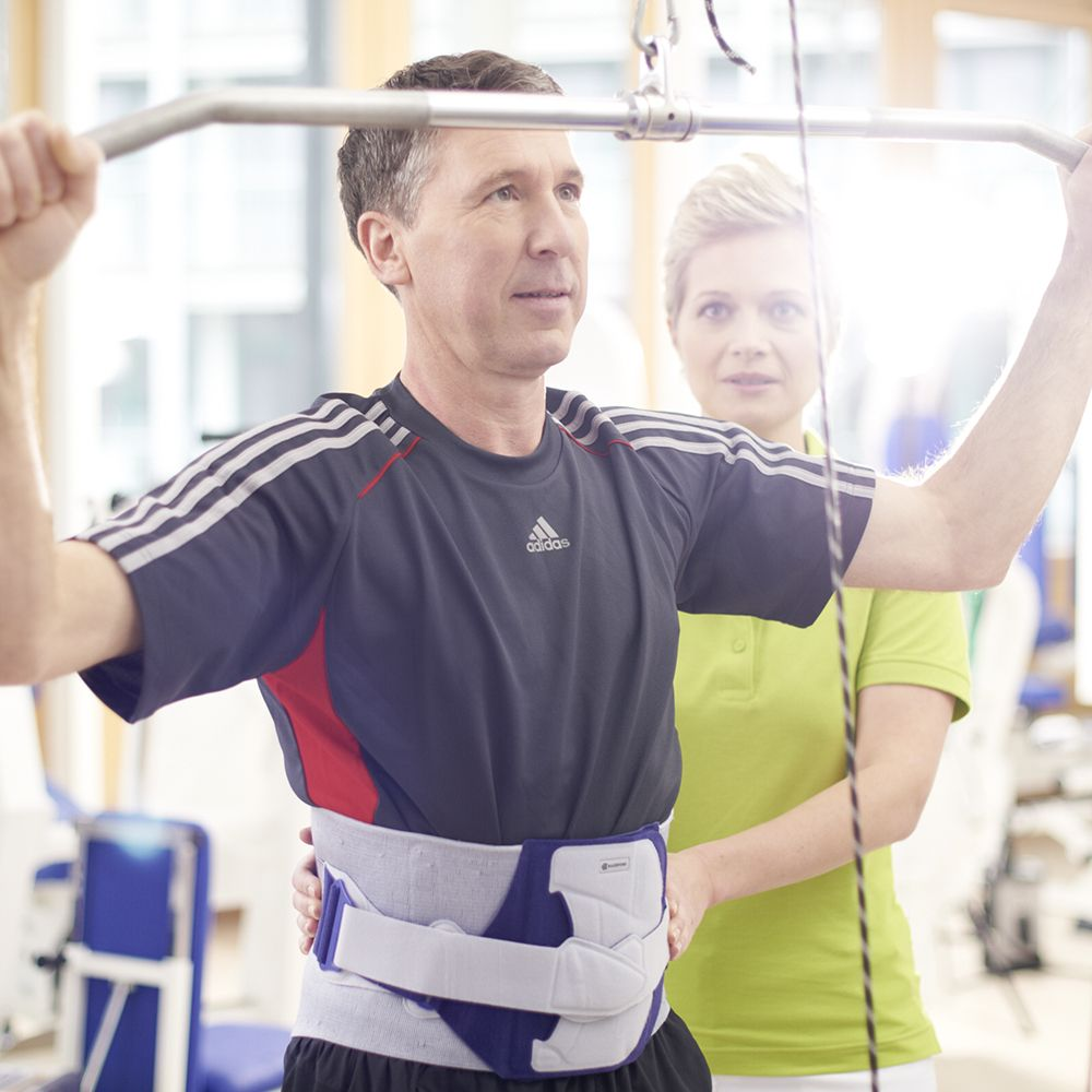 Man working with his trainer during spondyloarthritis treatment