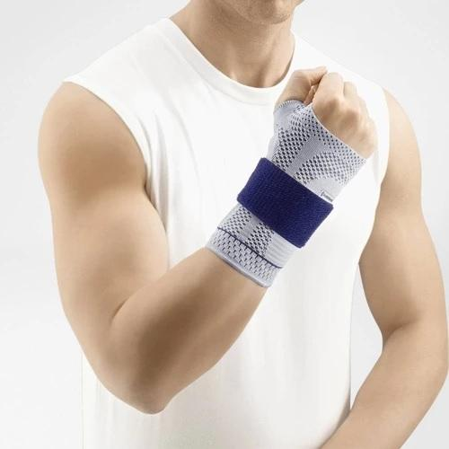 Wrist support in a colour combination of blue and grey and is worn on the right wrist. It is considered one of Bauerfeind Australia's best recovery wrist supports, ManuTrain Wrist Support.